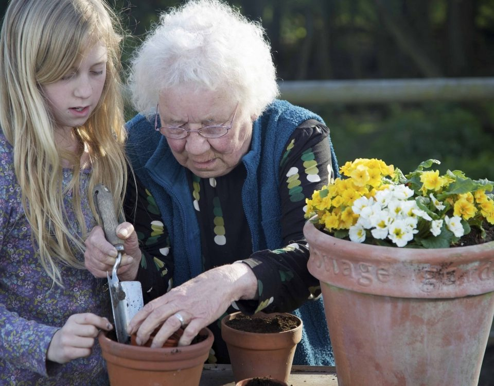 elderly gardening lady and child